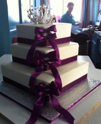 3 tier Buttericing wedding cake with purple ribbon