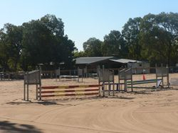 View across showjump arena to clubhouse