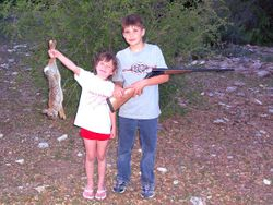 Tyler rabbit hunding with Michaela helping him show off his kill.