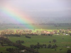 Rainbow and light shaft over valley