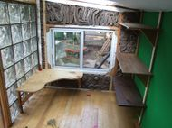 Interior of a tiny house. Cardboard, plexiglass, cobb and maple flooring are all reclaimed