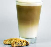Tall glass containing a layered coffee with creamy topping