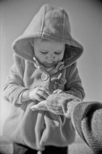 child looking down wearing hood