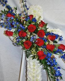 Cross sympathy spray with red roses and delphinium