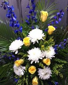 funeral spray with yellow roses and delphinium
