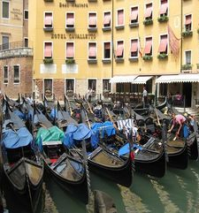 "womens tours.jpg alt=womens travel, gondolas lined up with blue covers, venice"">"