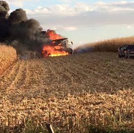 Combine fire in corn field
