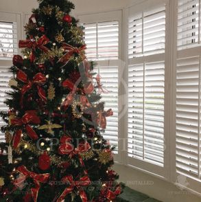 A Christams tree sets off our bespoke interior wooden shutters in this Essex home.