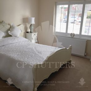 Our wood interior shutters, featured in pure white colour, installed in this bedroom, Shenfield Essex.