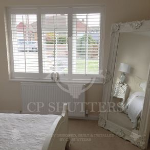 Quality wooden window shutters, installed in this shabby chic bedroom, essex.