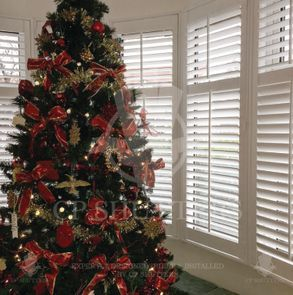 Another image of our wooden plantation shutters with a Christmas tree.