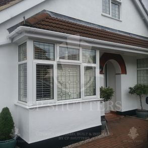 Our bespoke wooden shutters seen in a bay window, Essex