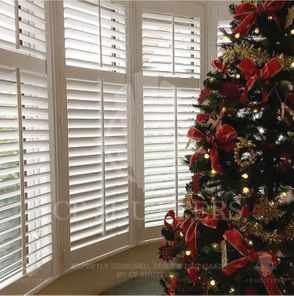 a Christmas tree in front of our beautiful white plantation shutters