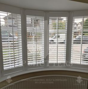 This is a curved bay window in Essex, UK featuring our bespoke interior wooden plantation shutters.