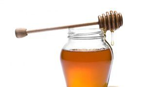 Honey in a jar, with a honey dipper.