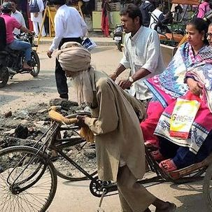 "src=""australian womens travel.jpg alt=womens tours,man with a bicycle carrying a heavy load , India"