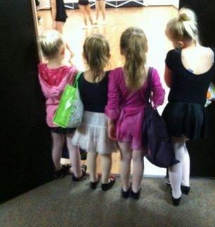 Children watch the older dancers practice.