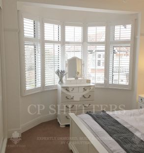 A bedroom in Essex, featuring our wooden window shutters essex, installed by CP Shutters.