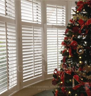 A Chrsitmas tree in front of our window shutters essex, fitted by CP Shutters.