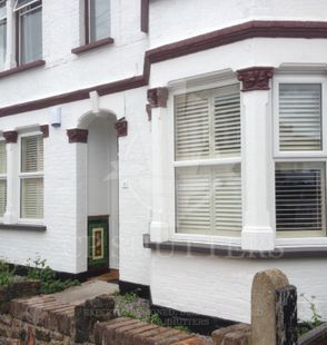 A bay window situated in Essex, dressed with our wooden window shutters, created by CP Shutters.