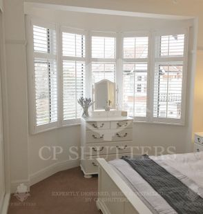 A bedroom in essex featuring our wooden interior plantation window shutters