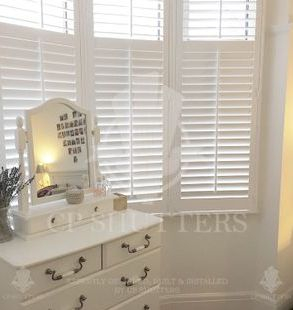 White wooden shutters fitted in a beautiful bedroom,. shutters in chelmsford Essex