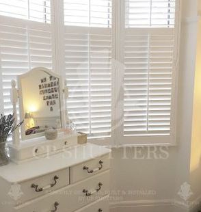 Our white wooden window shutters in a beautiful bedroom, Leigh-on-Sea, Essex by CP Shutters.