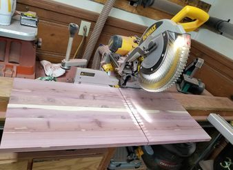 "picture of my Dewalt 12"" sliding Double bevel miter saw cutting a panel for a cedar chest"