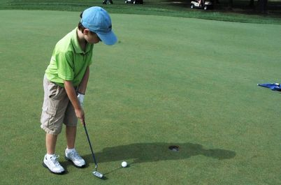 Youth golfer putting on green
