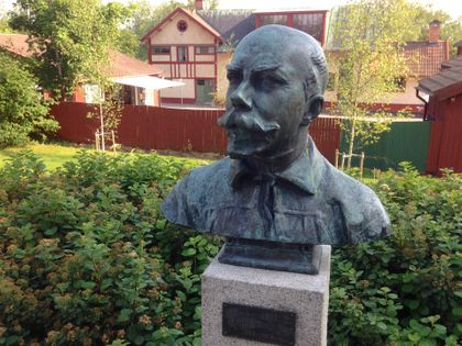 Byst av Carl Larsson med hans Lilla Hyttnäs i bakgrunden.