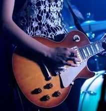 Female guitarist playing a Les Paul